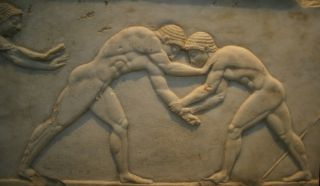 Ancient Greek Bas relief of men wrestling.