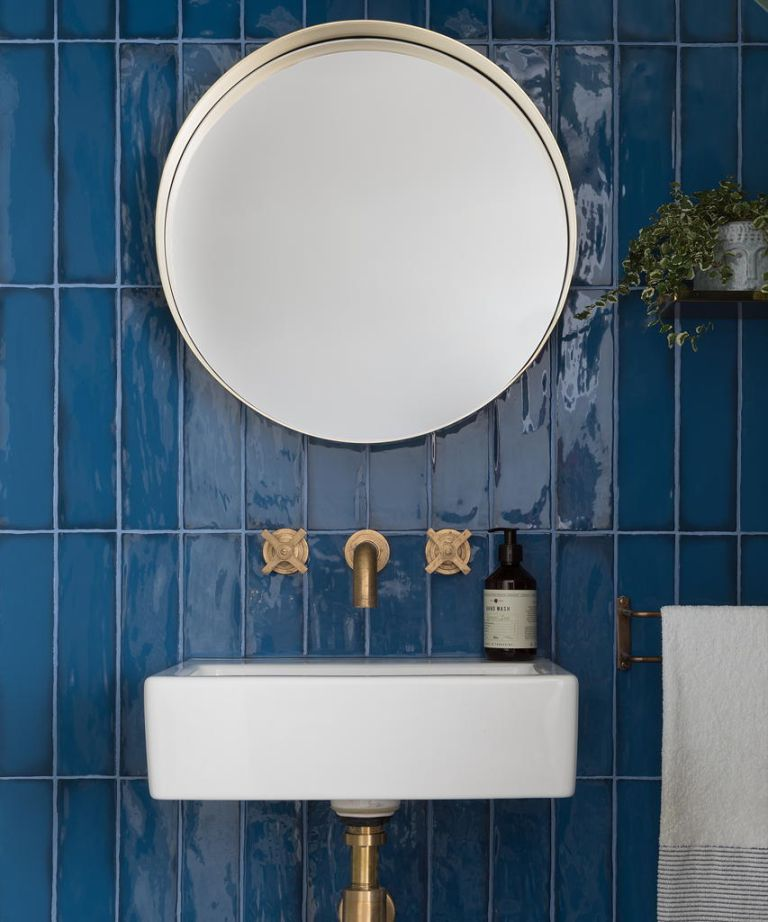 An example of how to tile a bathroom wall with blue metro tiles laid vertically behind a sink.