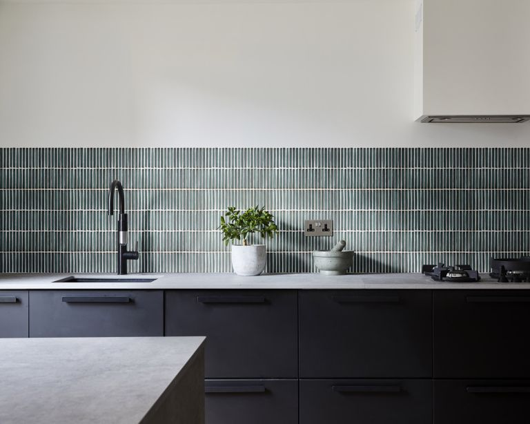 An example of kitchen tile costs showing a kitchen with gray cabinets and green wall tiles behind the worktop below a white wall