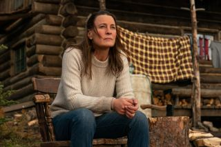 Edee (Robin Wright) sits on the steps leading to her cabin.