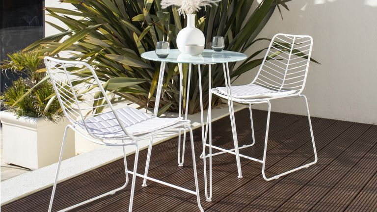 white metal bistro set from the Wayfair sale on a decked terrace
