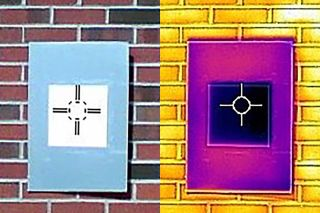 A photo taken by an infrared camera demonstrates how the white paint (dark square) cools the surrounding board (rectangle) below ambient temperature.