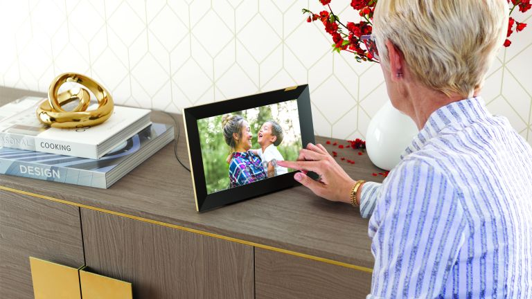 A woman looking at the best digital photo frame, the Nixplay