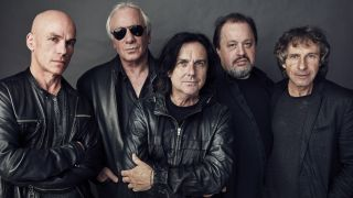 Line-up photo of Marillion, all dressed in black, in 2016