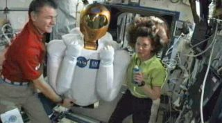 NASA astronaut Cady Coleman (right) and Italian astronaut Paolo Nespoli proudly display the newest resident of the International Space Station, the humanoid Robonaut 2 robot, to cameras on March 15, 2011.