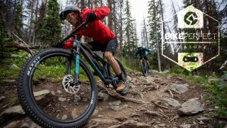 Two mountain biker rides over a rocky and rooty section of trail Canyon's new Lux Trail downcountry bike