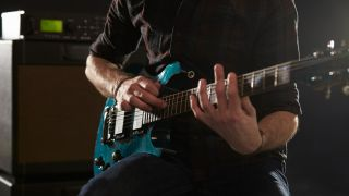 A guitarist taps their way along the fretboard