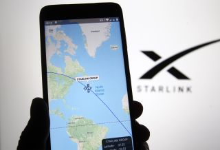Starlink tracker on phone with Starlink logo in background