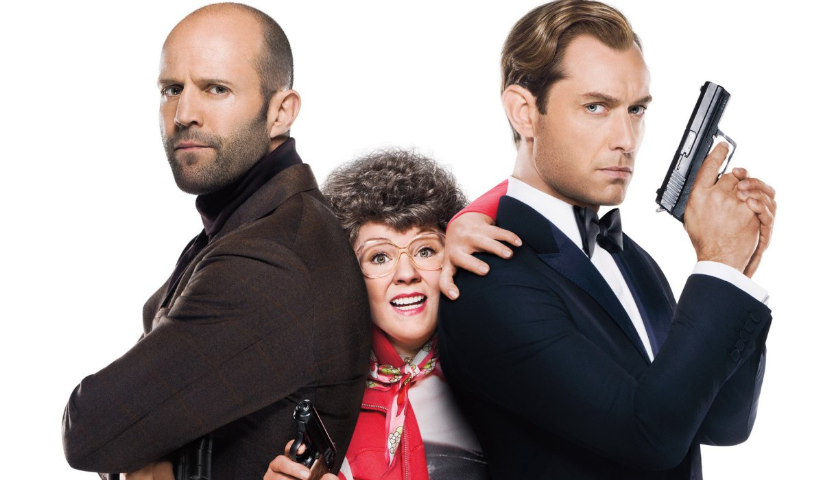 Spy Melissa McCarthy trying to escape from between Jason Staham and Jude Law
