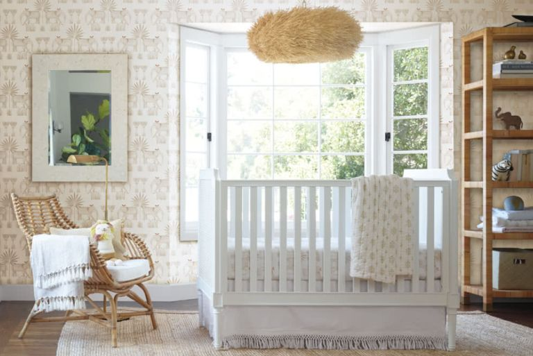 Neutral wallpaper in nursery with white wooden crib and wicker accent chair and textured shade