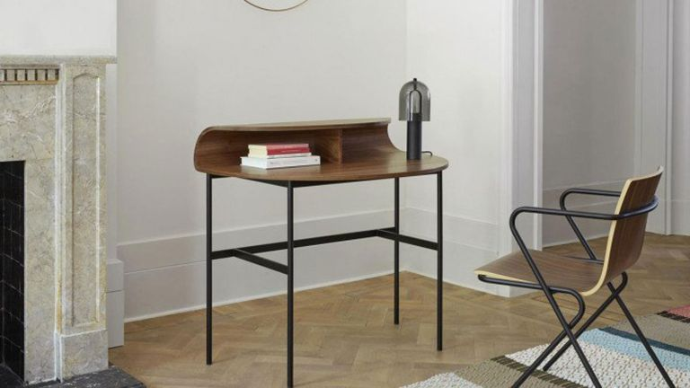 ligne roset wooden desk with metal legs on wooden floor with white walls and marble fireplace