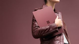 Woman carrying Microsoft Surface Laptop