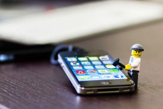 A Lego thief mini-figurine tries to break into an iPhone.