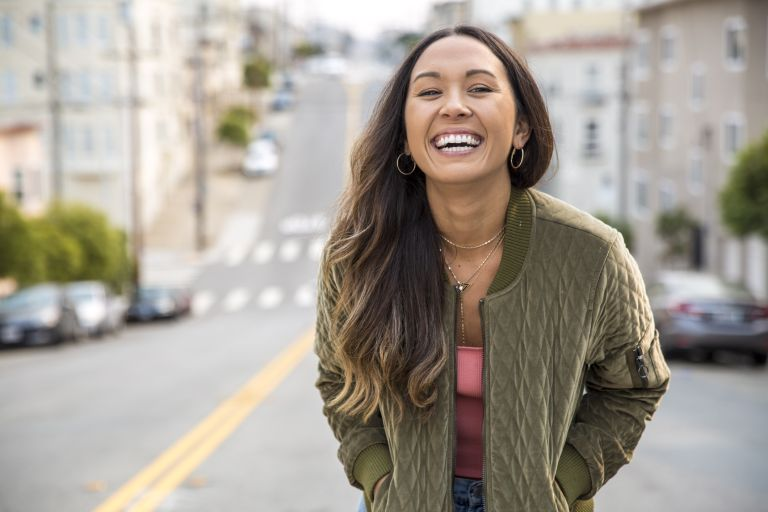 self-care day ideas - portrait of laughing young woman on the street