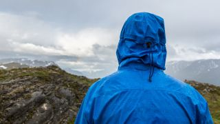 A person in a waterproof jacket looking out to the horizon