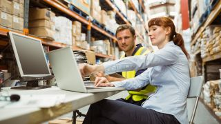 woman and man looking a warehouse management software