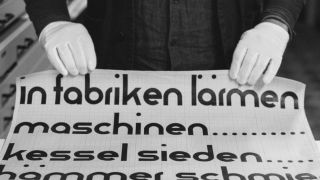 Gloved hands delicately handling a sheet of Bauhaus typography