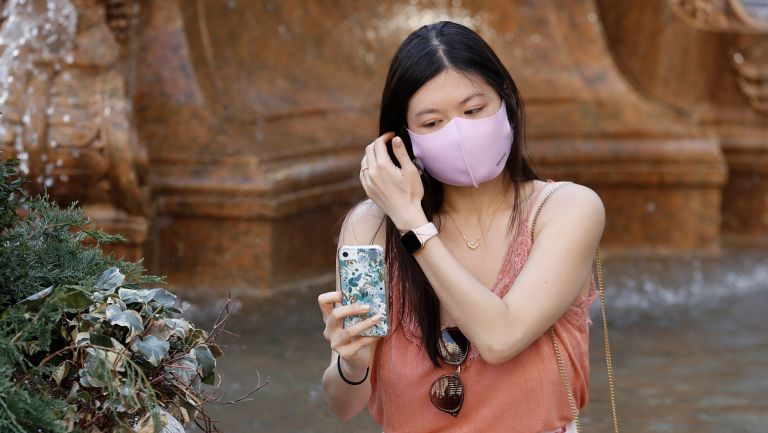 A woman wearing a protective mask looks at her cell phone in Bryant Park on March 26, 2021 in New York City.