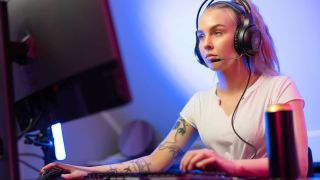 Woman playing PC using the best wired gaming headsets