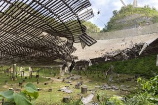 An image of the Arecibo Observatory's iconic radio telescope as seen between two serious cable failures that preceded the facility's collapse.