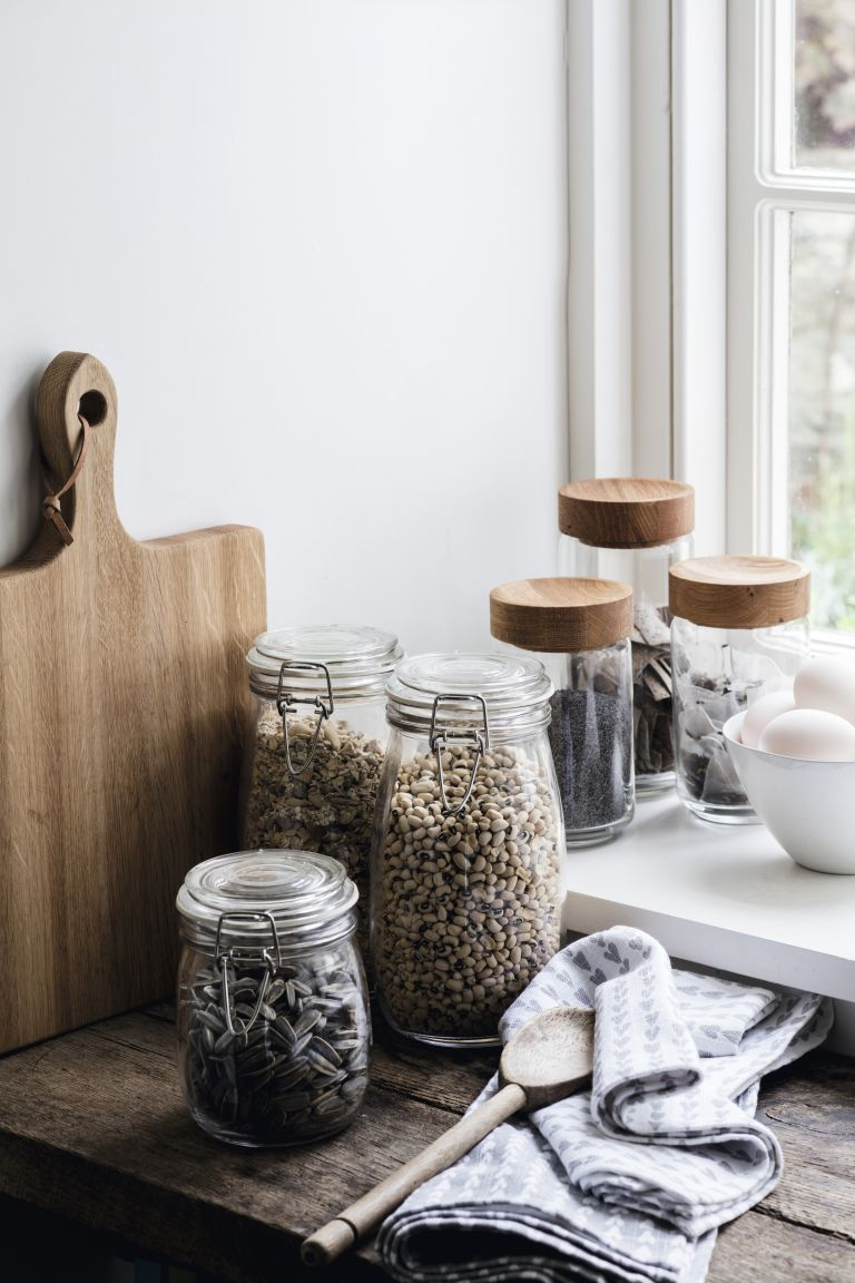 selection of storage jars filled with nuts, lentils and other dried goods on kitchen surface by The White Company