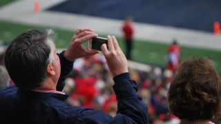 Man takes a picture on his smartphone at a stadium