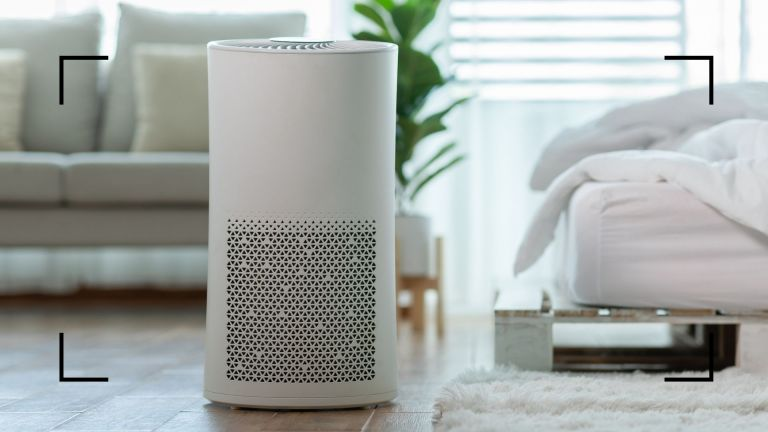 a white air purifier standing in a bedroom with the bed in the foreground