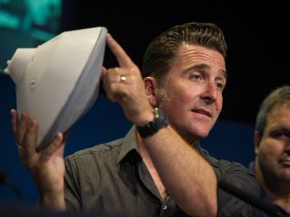 Adam Steltzner, NASA's Mars Science Laboratory entry, descent and landing phase lead, holds a model of the spacecraft.