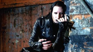 Marilyn Manson crouching by a brick wall