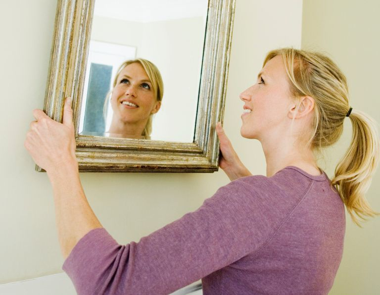 woman hanging a mirror
