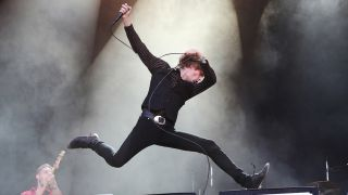Refused's Dennis Lyxzén leaping into the air onstage