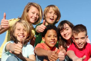 happy european kids making thumbs up sign