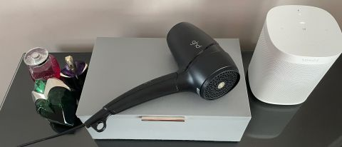 The GHD Flight hair dryer resting on a grey leath jewellery box on a glass dressing table