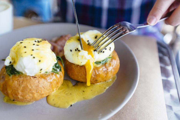 Close up of Eggs Benedict with liquid egg yolk running out