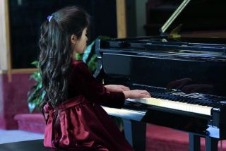 Child playing piano recital.
