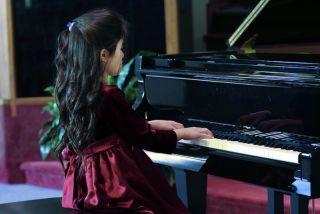 Child playing piano recital.