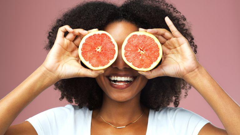 Woman holding grapefruit halves over her eyes