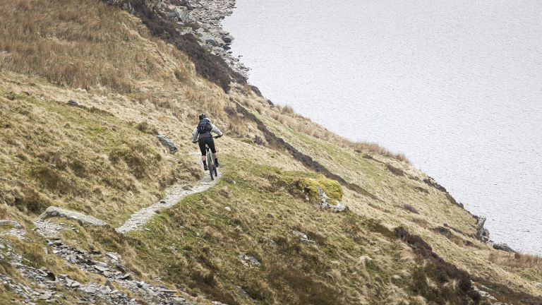best mountain bike: Person riding a Voodoo Bizango Pro mountain bike on a coastal trail