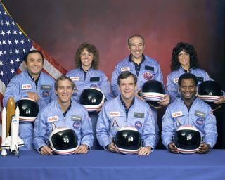 An official portrait shows the STS-51L crewmembers. Back row (L to R): Mission Specialist, Ellison S. Onizuka, Teacher in Space Participant Sharon Christa McAuliffe, Payload Specialist, Greg Jarvis and Mission Specialist, Judy Resnik. Front row (L to R):