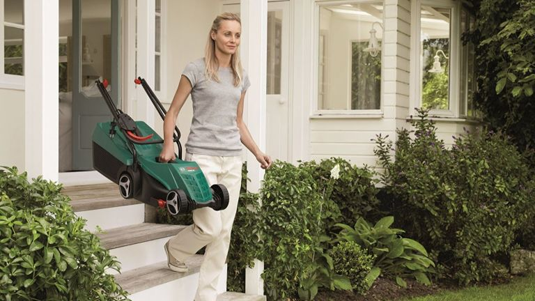 The best small lawnmowers: Bosch lifestyle image of woman carrying lawnmower