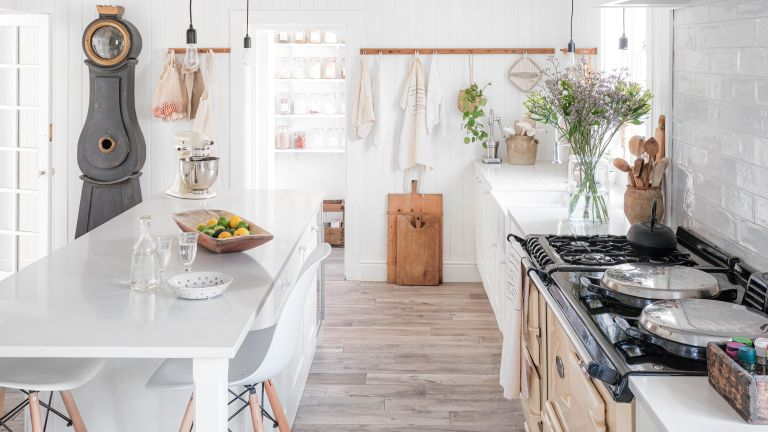 Rustic white kitchen with bare floorboards and an Aga