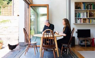 couple sat at table next to bifold doors