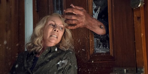 Michael Myers trying to grab Laurie Strode through a door