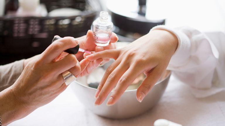 close up of woman having nails painted