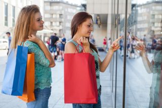 Two teen girls go shopping at upscale stores.