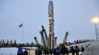 "A Soyuz rocket is readied for its cold weather launch from Baikonur Cosmodrome on Dec. 28, 2011 with the latest cluster of Globalstar second-generation spacecraft. Visible at left and right is the two-piece ""frame"" service tower system that will be raised"