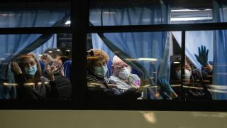 American citizens wave from a bus as they leave the quarantined Diamond Princess cruise ship at Daikoku Pier to be repatriated to the United States on Feb. 17, 2020 in Yokohama, Japan.