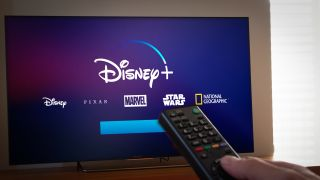 Barcelona, Spain. Jan 2019: Man holds a remote control With the new Disney+ screen on TV. Disney+ is an online video streaming subscription service, set to launch in the US in September.Illustrative - Image