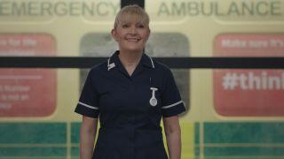 Casualty legend Duffy smiling broadly in her dark navy nurses uniform