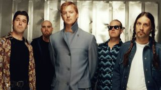 A photograph of Queens Of The Stone Age posing for a photo shoot including Gene Trautmann, Nick Oliveri, Josh Homme, David Catching and Hutch